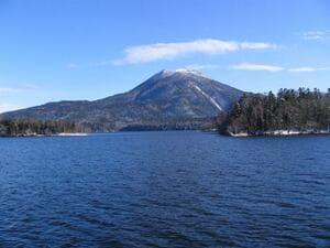 Une photo qui montre le lac d'Akan avec sa montagne