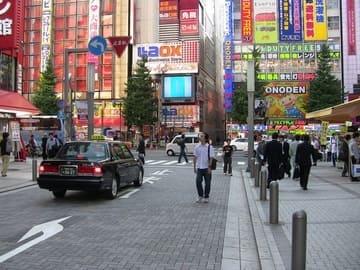 Une ruelle de Tokyo avec un taxi et des passants